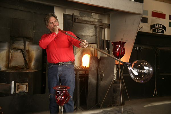an artisan at dollywood blowing glass