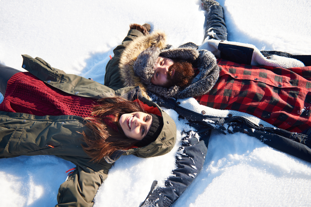 a man and woman making snow angels