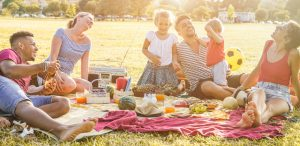 A family sitting together on a picnic blanket smiling in the sunshine