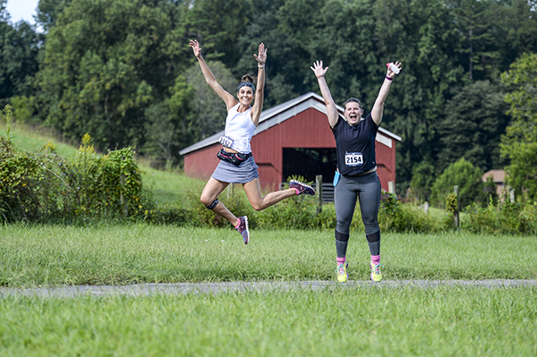 Two women jumping on a race course.