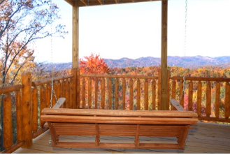 Swing on a covered porch with fall color mountain views