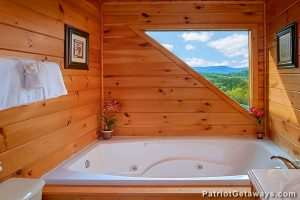 Jacuzzi tub with an asymmetrical window framing a mountain view at a cabin called Privacy & A View in Pigeon Forge, TN