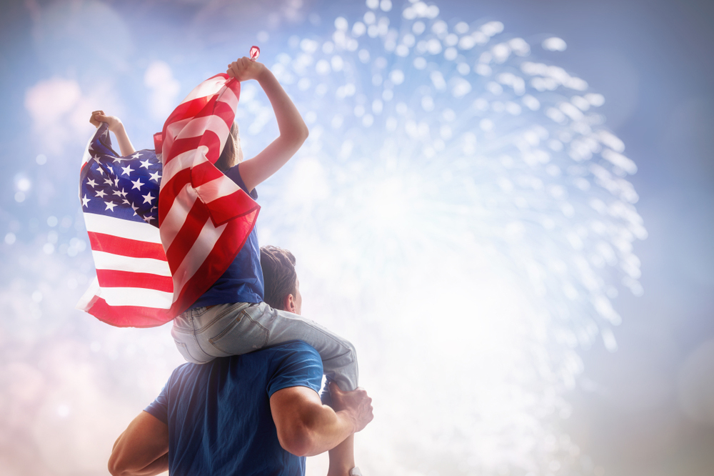 child on a man's shoulders watching fireworks