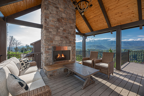 Covered deck with fireplace and mountain view