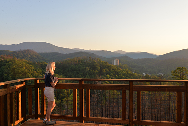 A woman stands on a deck at Anakeesta looking at Mt. LeConte at sunset