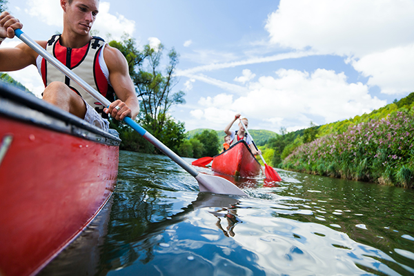 a man and a woman in red kayaks