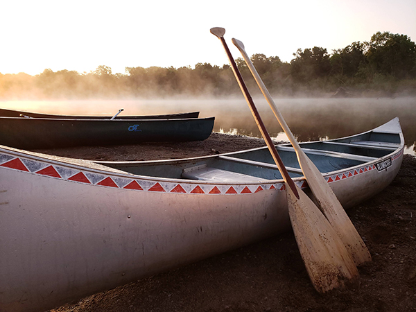 a silver canoe with two wooden paddles