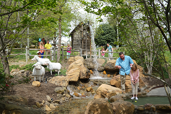 Parents and children playing mini golf