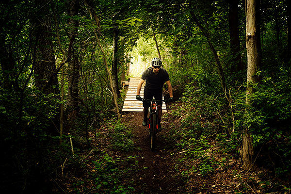 a mountain biker on a trail in a green tunnel