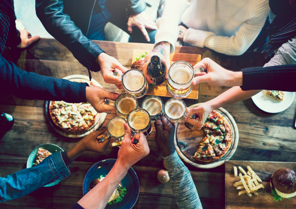friends toasting beer and food at a brewery